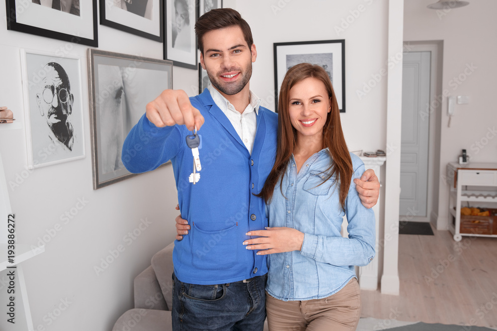 Fototapeta Couple standing at real estate sales office holding keys smiling happy