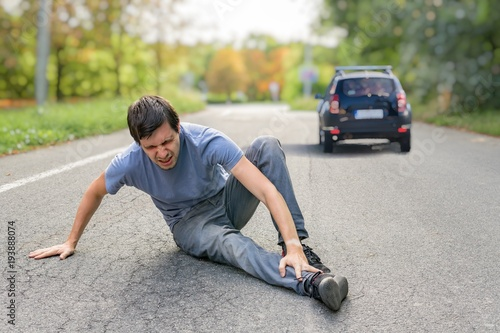 Fotografía  Hit and run concept. Injured man on road in front of a car.