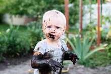 Child Playing In The Mud On Th...