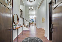 Chic Entrance Foyer With High Ceiling And White Walls.