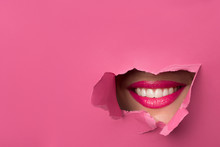 Close-up Of Female Lips With Pink Lipstick And A Broad Smile That Peeps Through The Pink Torn Paper