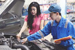 Car mechanic helping a customer fixing the car while holding a checklist