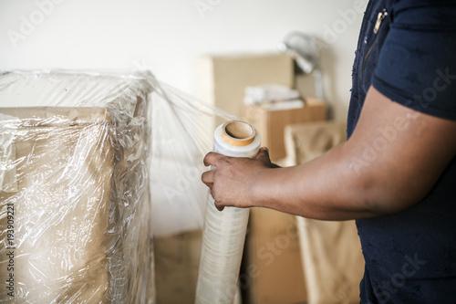 Fotomural  Black man moving furniture