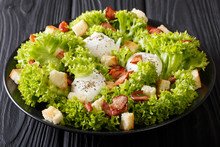 French Cuisine: Lyonnaise Salad Of Lettuce, Bacon, Croutons And Poached Eggs Close-up On A Plate On The Table. Horizontal