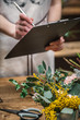 Anonymous employee of flower shop writing on clipboard standing at counter with flowers.