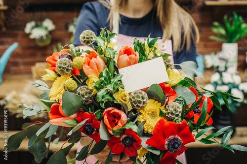 Tuinposter Bloemen Professional florist showing amazing vivid floral composition with blank white postcard.
