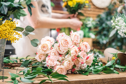 Foto op Canvas Bloemen Beautiful pink roses and green branches on working counter in floral shop.