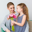 Happy Mother's Day, Women's day or Birthday background. Cute little girl giving mom, cancer survivor, bouquet of pink gerbera daisies. Mother and daughter smiling.
