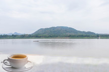 Abstract A Cup Of Coffee With The River, The Swamp,theboat,the Mountain, The Beautiful Sky And Cloud Background At Mekong River,international Border Between Chiang Khan District,Thailand And Laos PDR.
