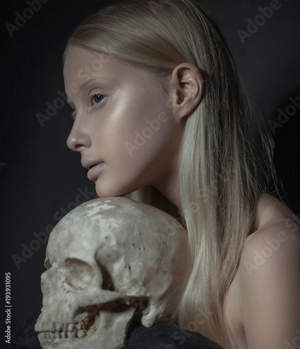 Portrait of young albino woman in profile with human skull in her hands Canvas-taulu