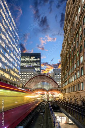 Foto auf AluDibond Bahnhof Einfahrender Zug in den Bahnhof von Canary Wharf in London am Abend