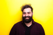 canvas print picture - Caucasian bearded hipster smiling on yellow background