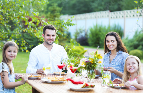 Láminas  Happy family of four people enjoying meal together outdoors