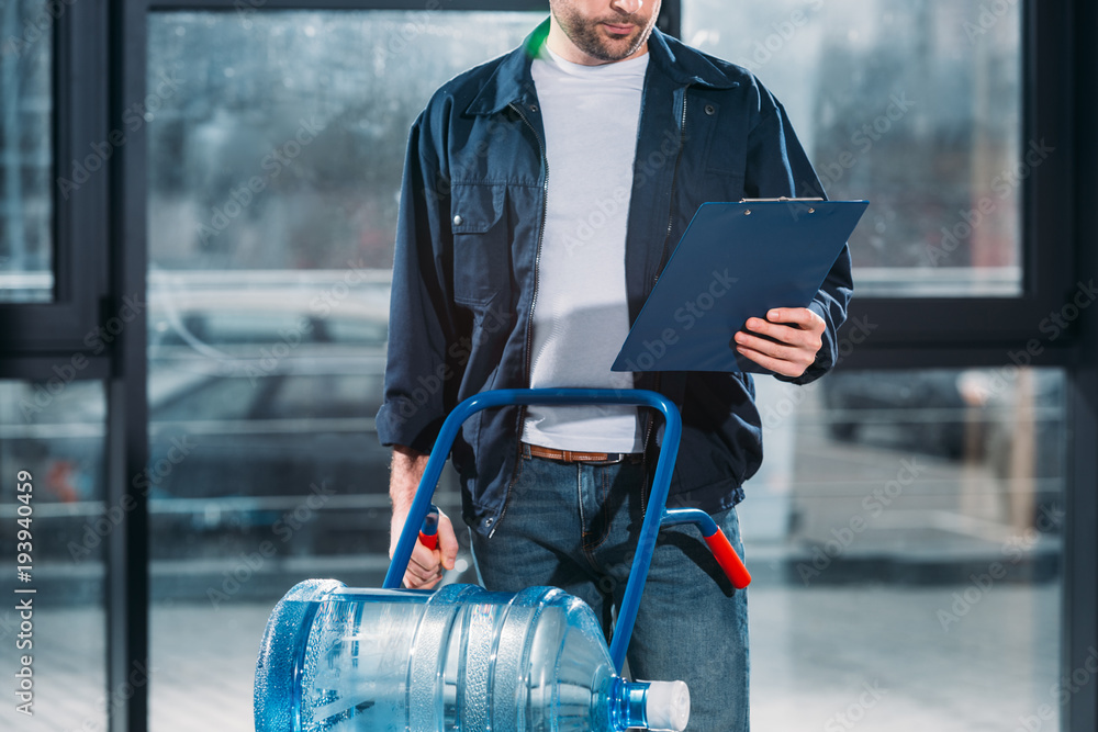 Obraz Loader looking at cargo declaration and holding delivery cart with water bottles fototapeta, plakat