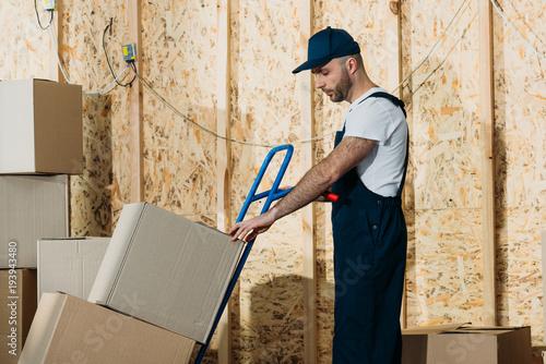 Cuadros en Lienzo Loader man adjusting cardboard boxes on delivery cart