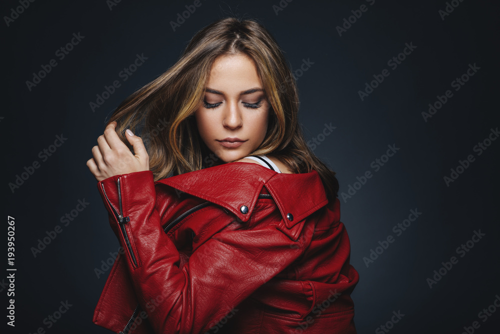 Fototapeta Portrait of a young woman in a red leather jacket in studio