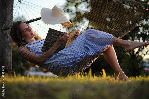 Deurstickers Beautiful young girl lying and reading a book