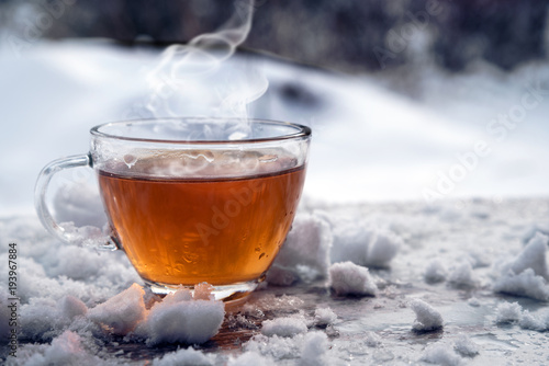 Poster Thee steaming hot tea in a glass cup is standing outside on a cold winter day with snow, copy space