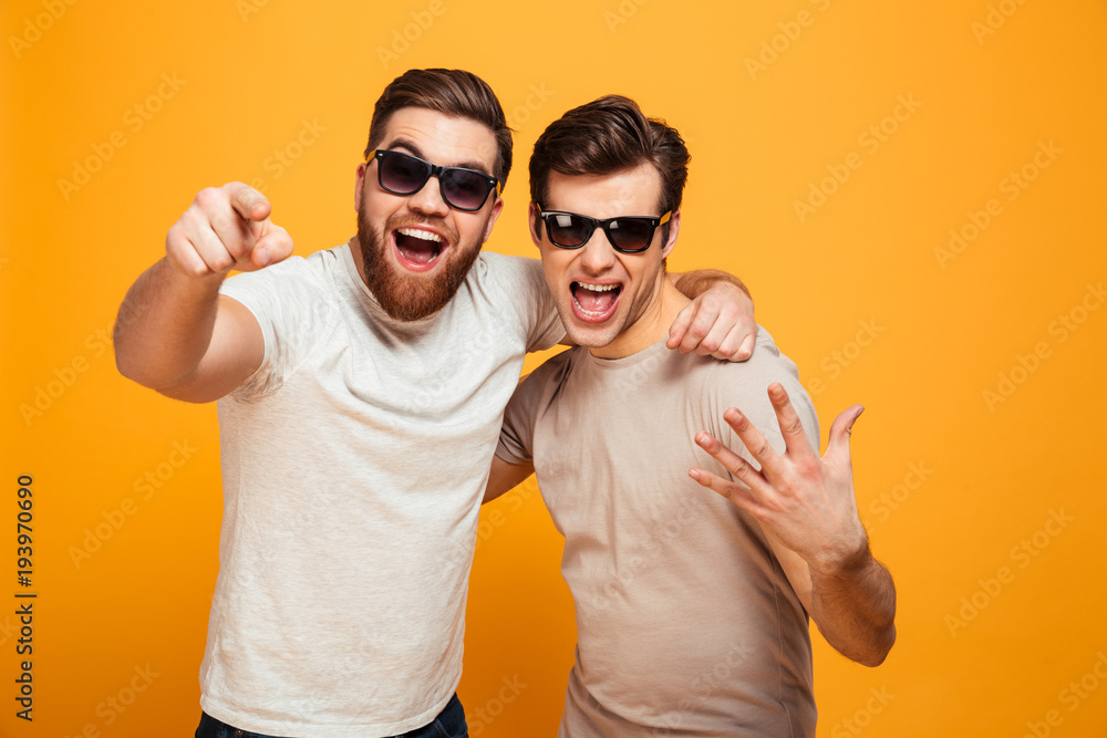 Fototapety, obrazy: Two happy men friends in casual t-shirts and sunglasses having fun together and pointing fingers on camera meaning hey you, isolated over yellow background