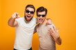 canvas print picture - Two happy men friends in casual t-shirts and sunglasses having fun together and pointing fingers on camera meaning hey you, isolated over yellow background
