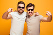 canvas print picture - Two happy men in casual t-shirts and sunglasses hugging and pointing fingers on camera meaning hey you, isolated over yellow background