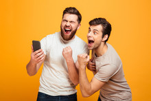 Image Of Two Bachelors Screaming And Rejoicing Win Of Football Team While Watching Game On Mobile Phone, Isolated Over Yellow Background
