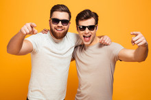 Two Happy Men In Casual T-shirts And Sunglasses Hugging And Pointing Fingers On Camera Meaning Hey You, Isolated Over Yellow Background