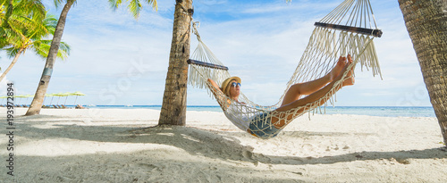 Woman in hat relaxing on hammock on the beach. Travel and vacation concept. Banner edition.