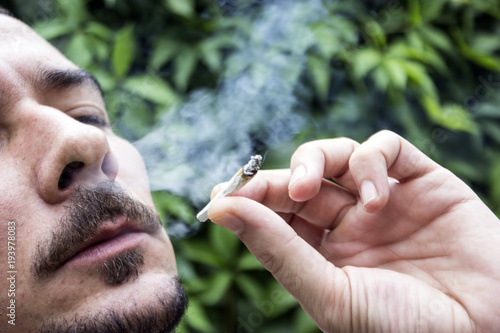 Photo  Close up of a unshaven man smoking a joint