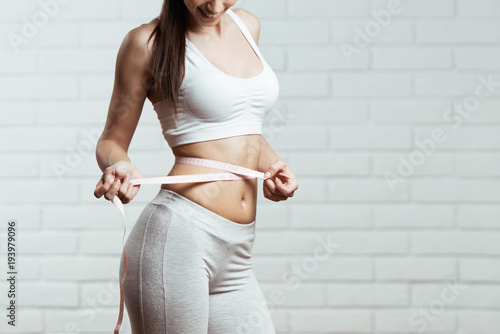 Beautiful, fit, young woman measuring her waist