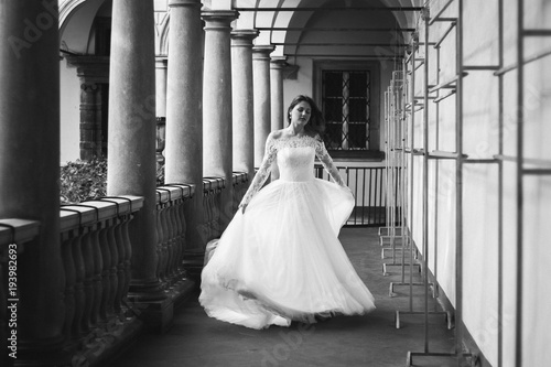 Printed kitchen splashbacks Fairytale World Beautiful bride with hair down in white lace tulle dress is running in ancient city. Girl holds her wedding dress in hand. Old town columns. Italian style architecture. Black and white photo.