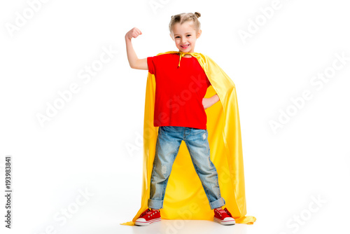 Photo  Smiling supergirl in yellow cape showing muscles on hand isolated on white