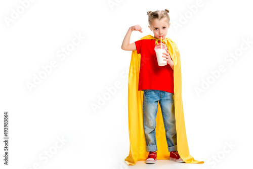 Supergirl in yellow cape drinking milkshake and showing muscles on hand isolated Canvas Print