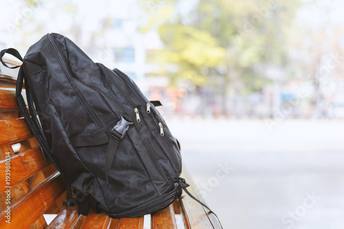 Obraz black backpack on wooden table in bus stations with soft-focus and over light in the background - fototapety do salonu