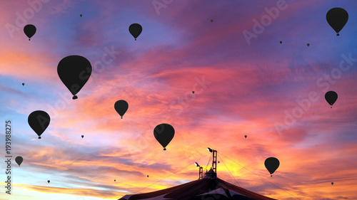 Black silhouettes of the hot air baloons over the circus tent on colorful sunset background