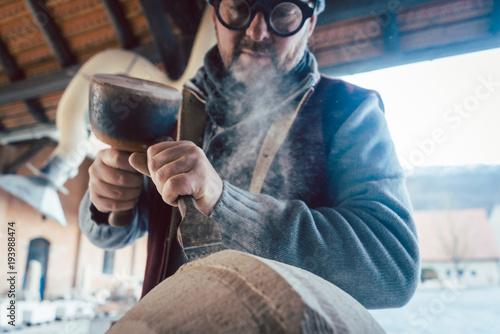 Stonemason chiseling stone in his workshop