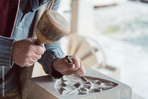 Steinmetz beim metzen eines floralen Musters im Stein
