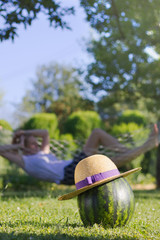 Straw hat on a watermelon and a girl relaxing in a hammock in the background.