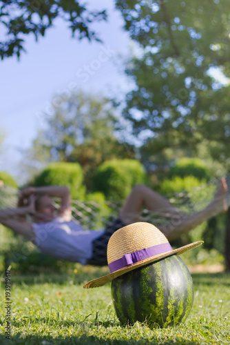 Poster Jardin Straw hat on a watermelon and a girl relaxing in a hammock in the background.