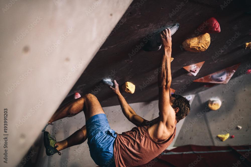 Fototapety, obrazy: Man climbing indoor boulder wall