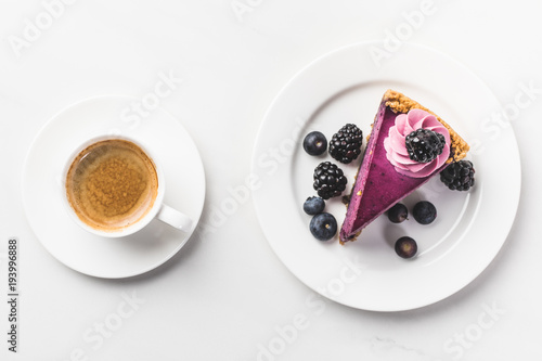 Fotografie, Obraz  top view of piece of cake with berries and cup of coffee isolated on white table
