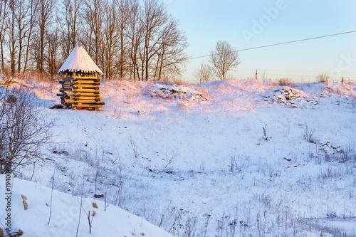 Zdjęcie XXL Drewniana wieża widokowa stoi na ośnieżonej górze. Zimowy krajobraz o zachodzie słońca. Dekoracje starych rosyjskich fortyfikacji w Funny Nicholas Fortress