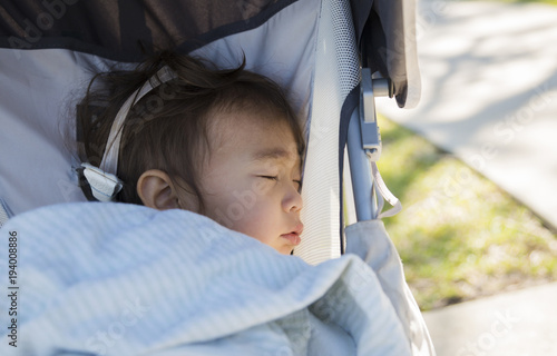Close-up of toddler sleeping in baby stroller at lawn