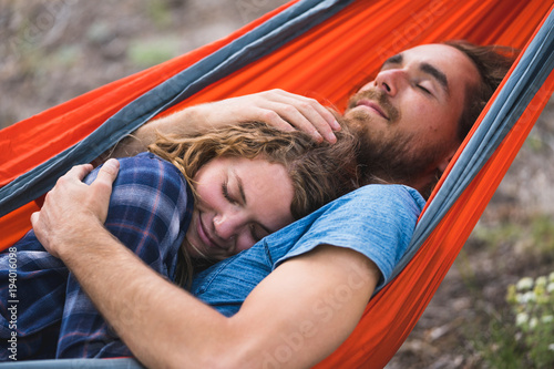 Man embracing woman while sleeping on hammock