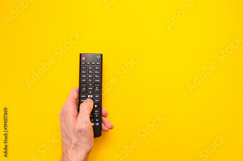 Fényképezés Television remote control in the hand isolated on yellow background