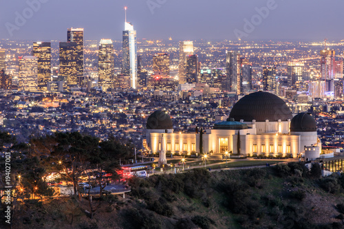 Photo Stands Los Angeles Griffith Observatory Park with Los Angeles Skyline at Dusk. Twilight views of the famous monument and downtown from Santa Monica Eastern Mountains. Los Angeles, California, USA.