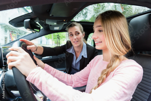 Fotografie, Obraz  Fahrschülerin am Steuer des Fahrschulwagens lernt Autofahren