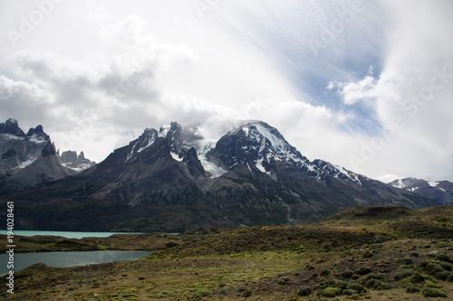 Plakat ośnieżone górskie szczyty torres del paine w chmurach i turkusowe jezioro
