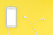 canvas print picture Smartphone with a white screen with headphones on a yellow background. Top view. Flat lay.