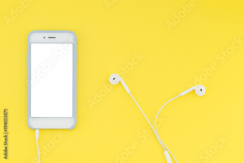 canvas print motiv - bodnarphoto : Smartphone with a white screen with headphones on a yellow background. Top view. Flat lay.
